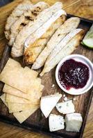 Tabla de quesos mixtos rústicos con pan tostado y mermelada de grosellas en bandeja de madera foto