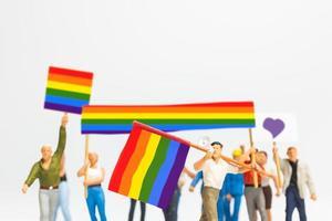Manifestante de personas en miniatura sosteniendo una bandera transgénero foto