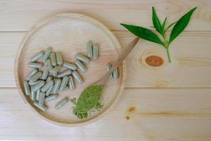 Kariyat en polvo en una cuchara de madera con cápsulas de hierbas. foto
