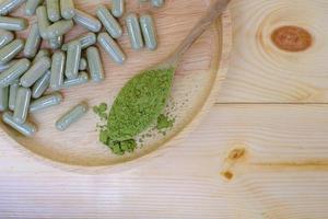 Kariyat en polvo en una cuchara de madera con cápsulas de hierbas en un plato de madera foto