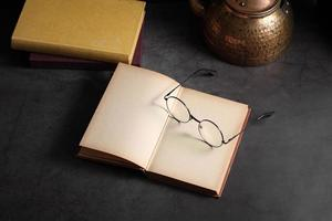 Old books and glasses open on table in library photo