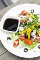 Traditional Greek salad with feta cheese and mixed organic vegetables on wooden table photo