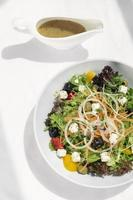 Greek salad with feta cheese and olives with citrus vinaigrette on wooden table photo
