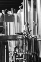 Industrial beer brewing equipment detail in brewery interior in black and white photo