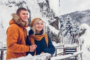 Feliz pareja amorosa caminando en Winter Park disfrutando de la nieve foto