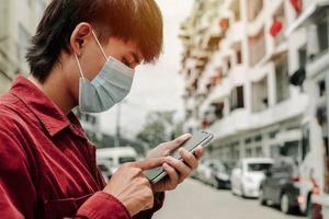 hombre con mascarilla médica usando el teléfono para buscar noticias. foto