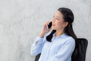 joven asiática hablando teléfono inteligente y sonrisa. foto