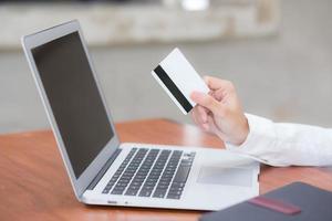 mujer asiática con tarjeta de crédito y compras en línea con computadora portátil. foto