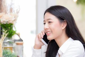 Young asian woman talking phone and smile in the coffee shop. photo