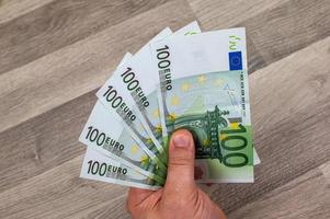 man's hand holding fanned 100 euro banknotes photo