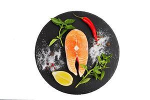Fresh salmon steak with lemon, tomato, olive oil and basil photo
