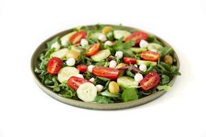 Arugula, tomato, cucumber, mozzarella and olive salad photo
