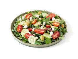Salad made with arugula, tomatoes, cucumbers, mozzarella and olives photo