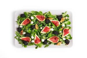 Plate with a salad of figs, blackberries, arugula, mozzarella photo