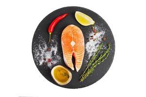 Fresh salmon steak with lemon, pepper and olive oil photo