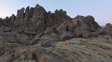 Aerial shot of a young man backpacker camping with his dog. video