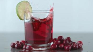 Ice splashing into cranberry juice in slow motion video