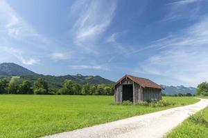 Paisaje de pradera bávara con cabaña de madera, camino de luz y cielo azul foto