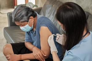 An Asian female doctor is vaccinating an elderly man at home. photo