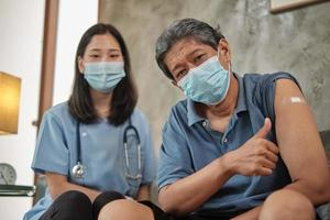 Elderly patient with face mask thumb up when vaccinated. photo