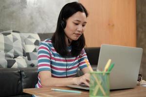 mujer asiática que usa la computadora portátil para el trabajo desde casa y el aprendizaje en línea. foto