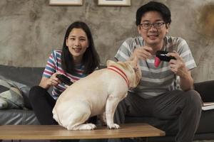 pareja asiática está jugando videojuegos y un perro mascota cerca. foto