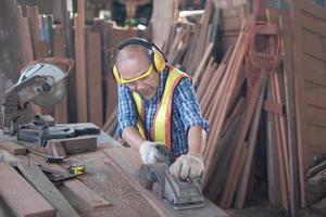 Carpintero masculino asiático senior está trabajando en la fábrica de madera. foto