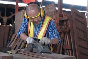 Hombre asiático carpintero maduro en fábrica de madera. foto