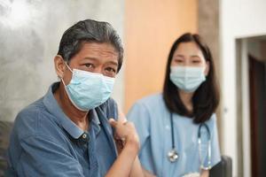 El paciente anciano señala con el dedo al brazo después de la vacunación. foto