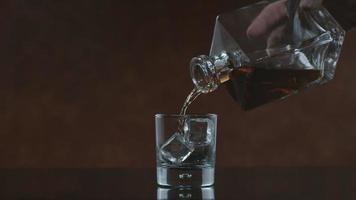 El whisky se vierte en un vaso en cámara lenta. video