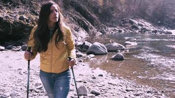 Mujer joven durante una caminata nordic walking a bordo de un río video