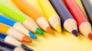 Primer plano de lápices de colores sobre fondo amarillo, formación de dibujo. foto