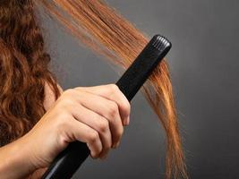 Girl smooths curly hair with a hair straightener, curling iron. photo