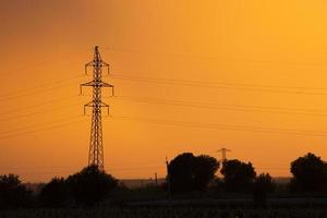 Electricity transmission pylon against orange sky photo