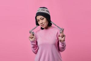 Portrait of angry woman standing looking at camera on pink background photo