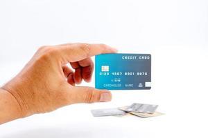 Mano sujetando tarjetas de crédito bancarias sobre fondo blanco. foto