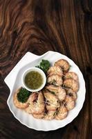 Langostinos hervidos frescos con salsa picante de cítricos en la mesa de madera foto