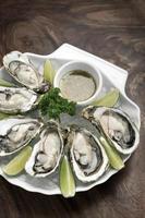 seis ostras frescas con rodajas de lima y salsa vinagreta de cítricos foto