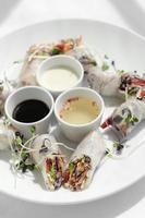 Rollitos de primavera veganos de vegetales frescos asiáticos con salsas en Vietnam foto