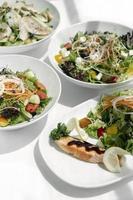 Ensaladas orgánicas frescas mixtas en tazones sobre la mesa de restaurante blanco foto