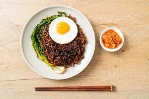 Korean spicy black sauce instant noodles with fried egg and kimchi photo