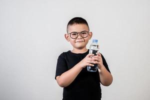 Chico divertido con botella de agua en foto de estudio