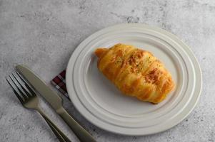 Sausage bread roll with hotdog on white plate photo