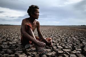 An elderly man sat hugging his knees bent on dry soil. photo