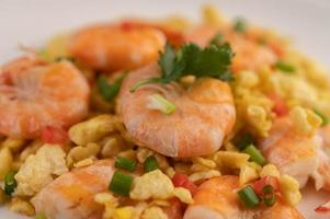Stir fried eggs with shrimp on a white plate. photo