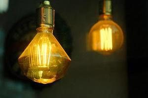 glowing yellow tesla decorative glass light bulb in the dark photo