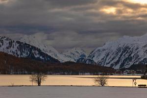 Otoño paisaje de montaña en un lago en el valle de la Engadina en el crepúsculo foto