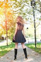 Beautiful woman in skirt turns to road photo