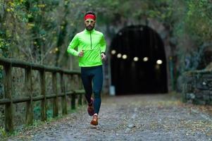 Hombre atleta se ejecuta en carril bici entre túneles en el otoño foto