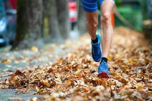 Detalle de zapatos de corredor entre las hojas. foto